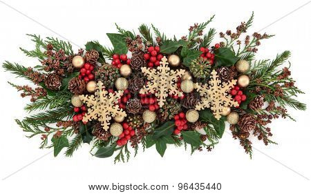Christmas gold snowflake bauble decorations, holly, mistletoe, ivy, pine cones and traditional greenery over white background.
