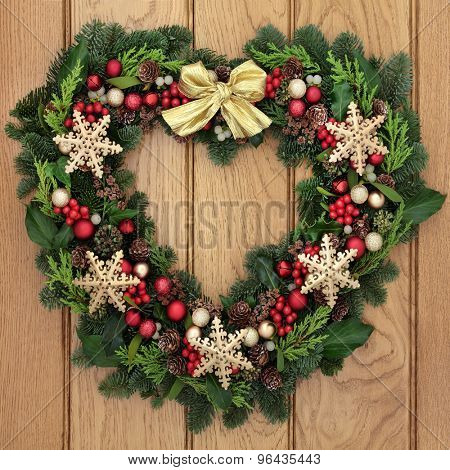 Christmas heart shaped wreath with gold snowflake bauble decorations, bow, holly, mistletoe and winter greenery over oak front door background.
