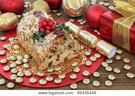 Stollen christmas cake with red and gold decorations and holly over oak background.