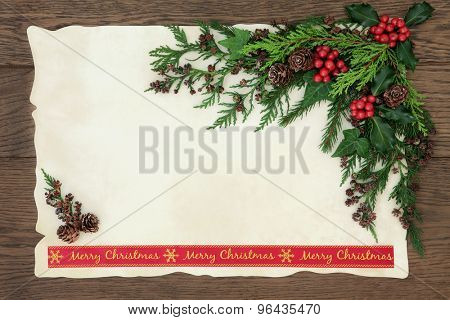 Background border with merry christmas ribbon, holly, ivy, fir and pine cones on parchment paper over old oak wood.