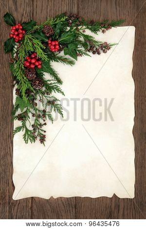 Christmas background border with holly, ivy, fir and cedar cypress  on parchment paper over old oak wood.
