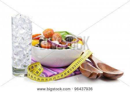 Fresh healthy salad, glass of water and kitchen utensil. Healthy food isolated on white background