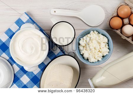 Dairy products on wooden table. Sour cream, milk, cheese, eggs and yogurt. Top view