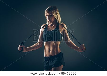 Sport, activity. Cute woman with skipping rope. Muscular girl black background.