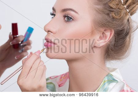 Makeup artist applies lipstick. Beautiful woman face.