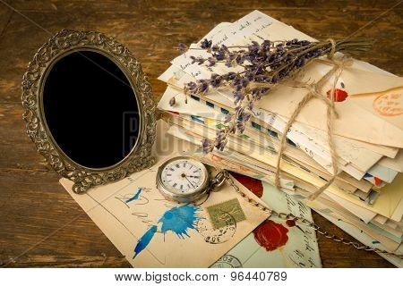 Empty antique picture frame and a pile of old letters on a wooden table
