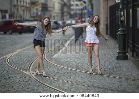 Two young best girlfriends walk along the tram tracks in the evening old town.