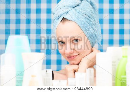 Girl Is Smiling Surrounded By Various Cosmetics In Bathroom
