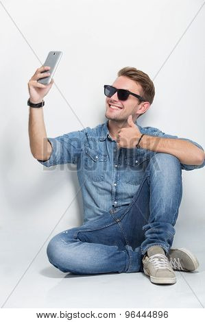 Young Man Sitting On The Floor Taking Self Camera