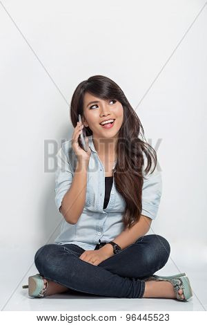 Young Woman Sitting On The Floor While Calling With Her Smartphone