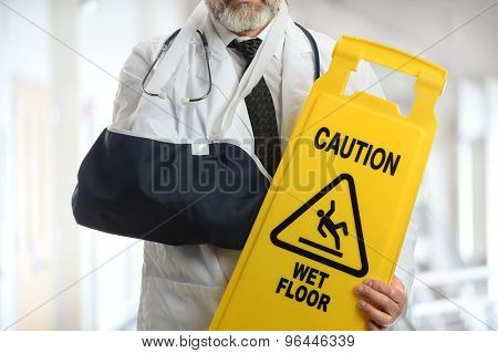 Senior doctor holding caution sign while wearing elbow sling inside building