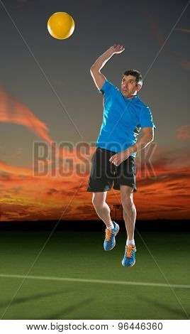 Adult Hispanic man serving volleyball at sunset