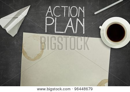 Action plan concept on black blackboard with empty paper sheet
