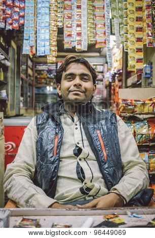 MUMBAI, INDIA - 05 FEBRUARY 2015: Indian vendor sits in shop with gutka hanging in background. Post-processed with grain, texture and colour effect.