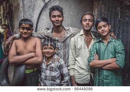 MUMBAI, INDIA - 12 JANUARY 2015: Five Indian boys from Dharavi slum stand in street. Post-processed with grain, texture and colour effect.