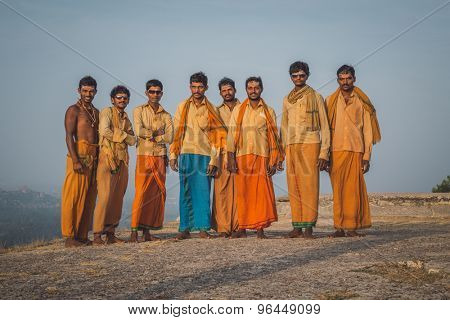 HAMPI, INDIA - 03 FEBRUARY 2015: Eight pilgrims gather for a photo on hilltop dressed in orange clothes. Post-processed with grain, texture and colour effect.