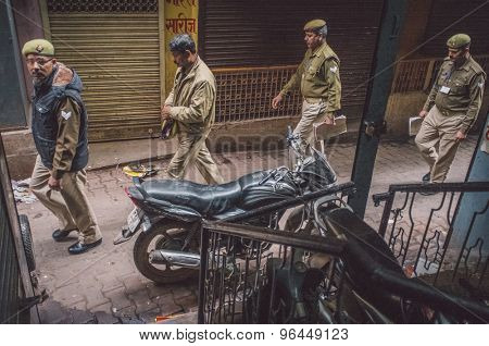 VARANASI, INDIA - 20 FEBRUARY 2015: Four Indian policemen walk on street of old part of Varanasi and pass by parked motorcycle. Post-processed with grain, texture and colour effect.