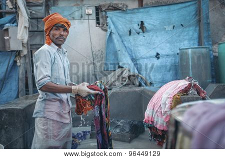 MUMBAI, INDIA - 10 JANUARY 2015: Indian worker washing a sari in Dhobi ghat. Post-processed with grain, texture and colour effect.