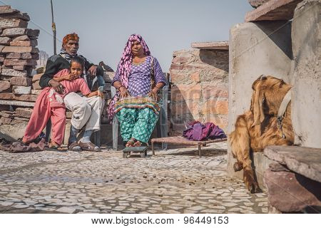 JODHPUR, INDIA - 09 FEBRUARY 2015: Grandparents rest with granddaughter in courtyard of home with goat sitting close by. Post-processed with grain, texture and colour effect.