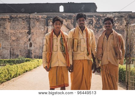 HAMPI, INDIA - 30 JANUARY 2015: Three pilgrims in front of Queen's bath. Post-processed with grain, texture and colour effect.