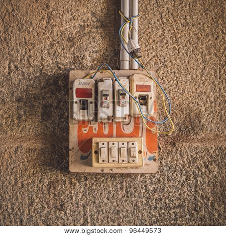 HAMPI, INDIA - 28 JANUARY 2015: Small safety fuse with switches on stone wall. Post-processed with grain, texture and colour effect.