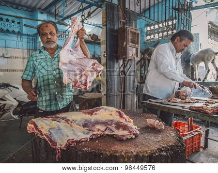 MUMBAI, INDIA - 11 JANUARY 2015: Butcher shows peace of mutton while fellow worker packs meat next to him. Post-processed with grain, texture and colour effect.