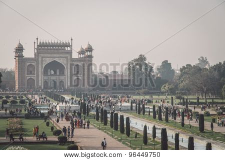 AGRA, INDIA - 28 FEBRUARY 2015: AGRA, INDIA - 28 FEBRUARY 2015: View of North side of Great Gate from Taj Mahal with visitors. Post-processed with grain, texture and colour effect.