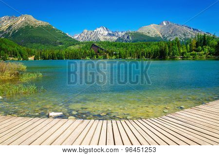 Wooden platform with view at clear mountain lake