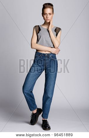 Full Length Shot Of A Woman In A Gray Shirt And Blue Jeans