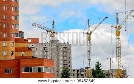 Cranes And Building Construction On The Background Of Clouds