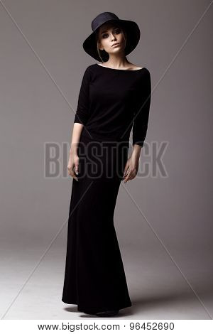 Full Length Shot Of A Woman In Long Black Dress And Hat