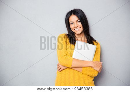 Smiling young woman standing with laptop over gray background. Looking at camera