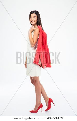 Full length portrait of a smiling woman holding jacket on shoulder isolated on a white background. Looking at camera