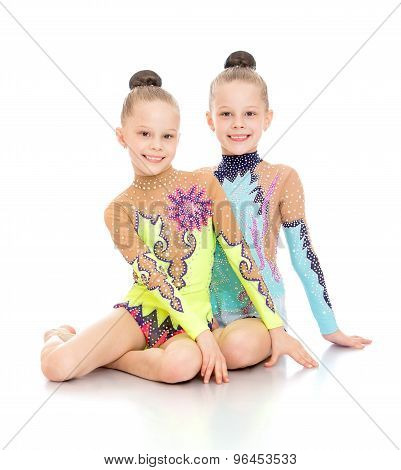 Two gymnasts sitting on the floor