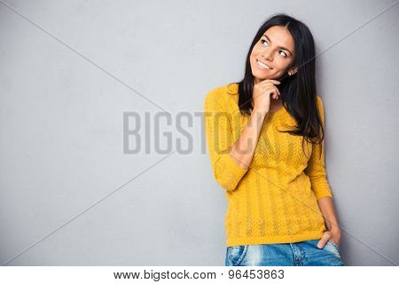 Happy thoughtful woman looking up at copyspace over gray background