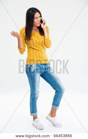 Full length portrait of angry woman in casual cloth talking on the phone isolated on a white background