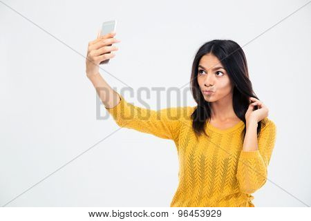 Young beautiful woman making selfie photo on smartphone isolated on a white background