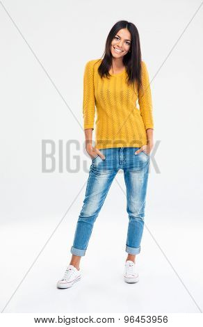 Full length portrait of a cheerful casual woman standing isolated on a white background. Looking at camera