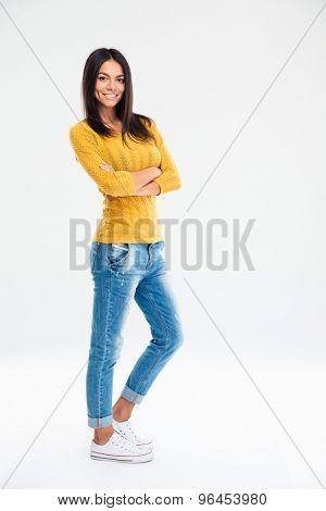 Full length portrait of a smiling cute woman standing with arms folded isolated on a white background