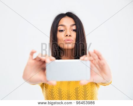 Happy beautiful woman making selfie photo on smartphone isolated on a white background