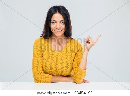 Smiling young woman sitting at the table and pointing finger away over gray background. Looking at camera