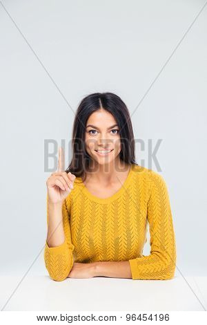Smiling casual woman sitting at the table and pointing finger up. Having idea. Looking at camera
