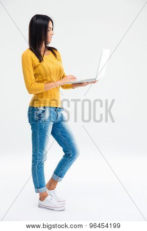 Full length portrait of a smiling young woman standing and using laptop computer isolated on a white background