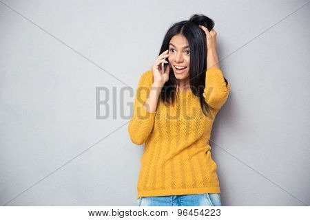 Amazed young woman talking on the phone over gray background