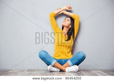 Happy thoughtful woman sitting on the floor with crossed legs and looking up over gray background