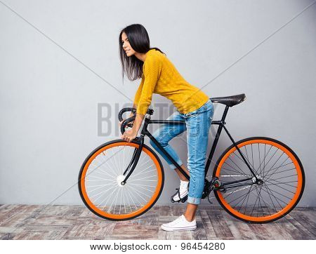 Full length portrait of a charming woman with bicycle on gray background. Looking at camera