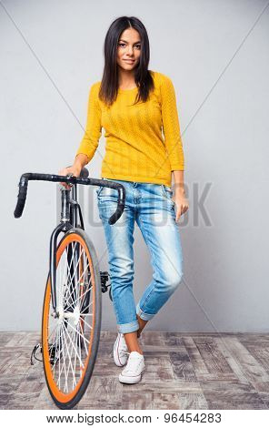 Full length portrait of a happy woman stnading with bicycle on gray background and looking at camera