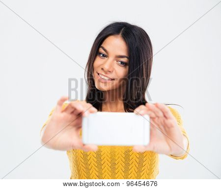 Portrait of a smiling young girl making selfie photo on smartphone isolated on a white background