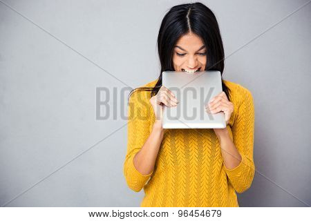Angry woman biting tablet computer over gray background
