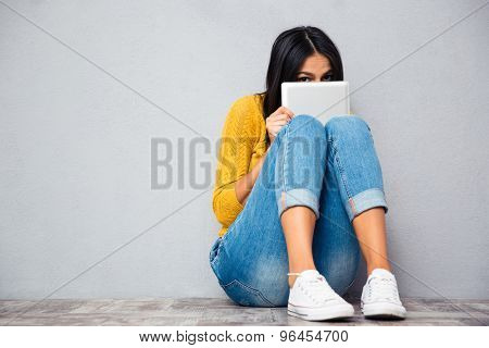Funny woman sitting on the floor and covering her face with tablet computer on gray  background